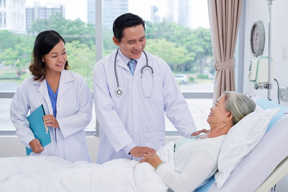 doctor and nurse talking to senior patient recovering