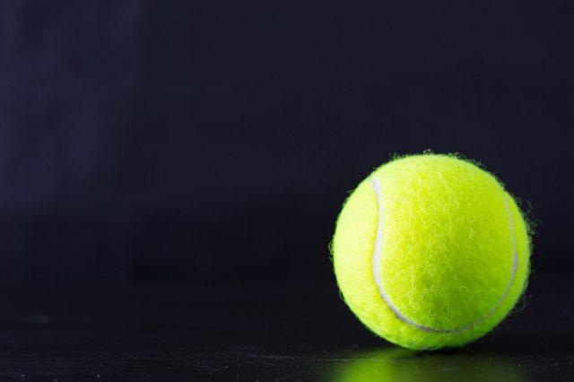 A tennis ball on a black background.