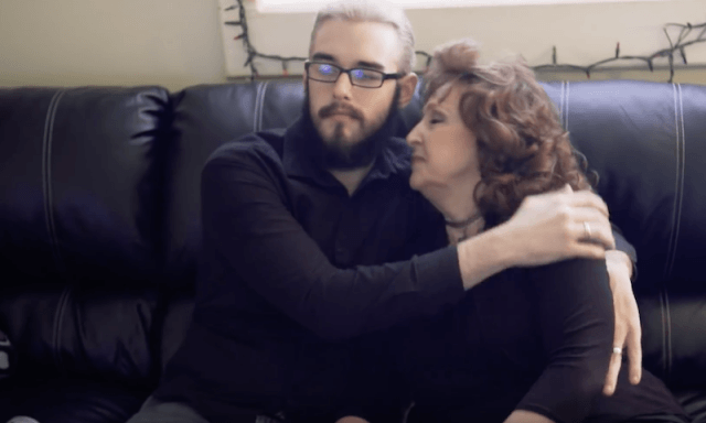 The couple hugs on a couch.