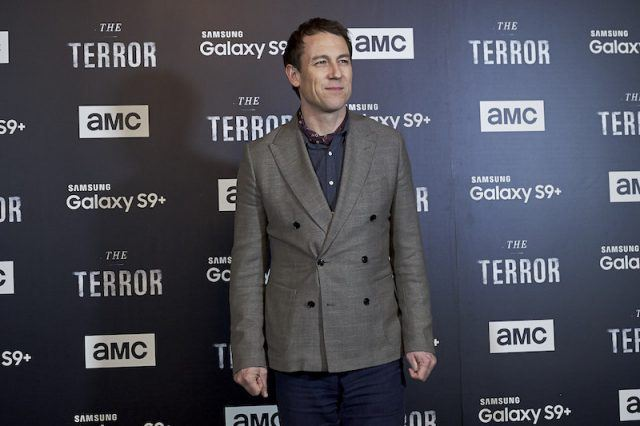 Tobias Menzies stands on a red carpet.
