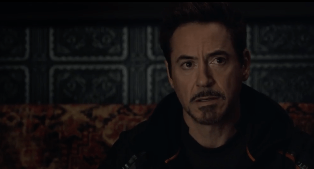 Tony Stark sitting in a dark room.