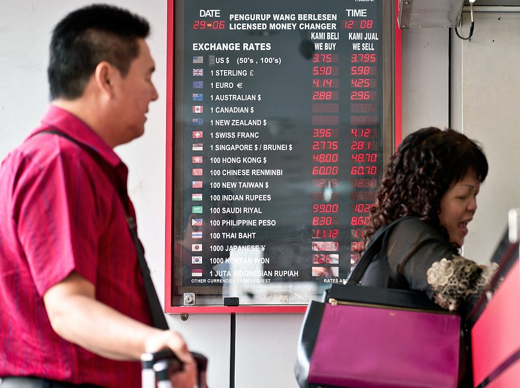 Tourists stand in front of a foreign currency exchange rate display board