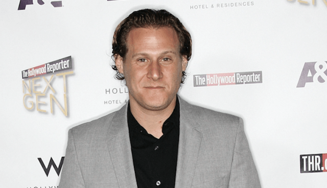 Trevor Engelson stands on a red carpet in a gray silver.