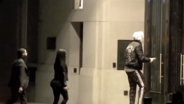 Tristian being followed by a woman and man as he enters a hotel.