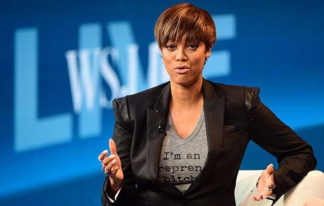 Tyra Banks sits on stage while on a panel.