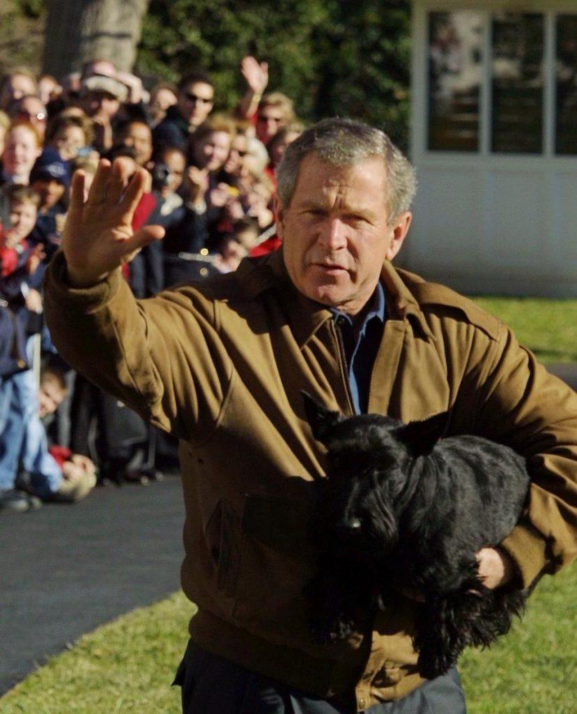 US President George W. Bush, holding pet dog Barney, waves to the crowds before leaving the White House