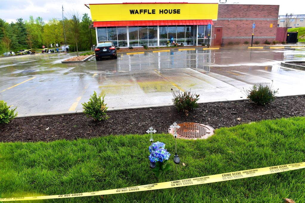 Waffle House with police tape and people walking towards it