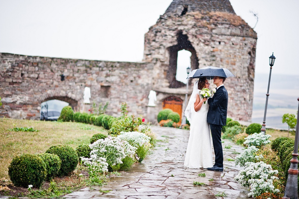 Wedding couple walking under rain