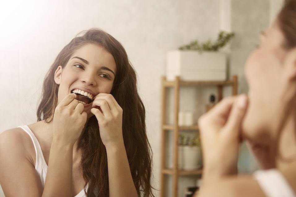 Woman is using dental floss