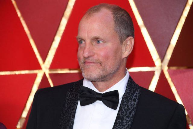 Woody Harrelson wearing a black tuxedo and bowtie while on a red carpet.