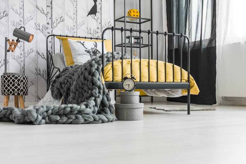 Grey woolen handmade blanket falling off the bed