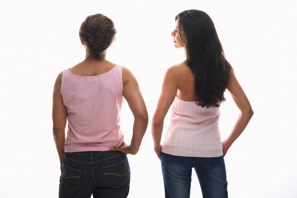 Young woman and mature woman standing with hands on hips