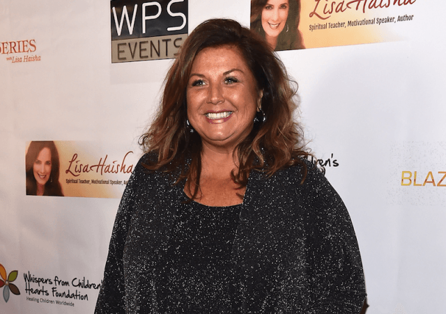 Abby Lee Miller smiling on a red carpet.