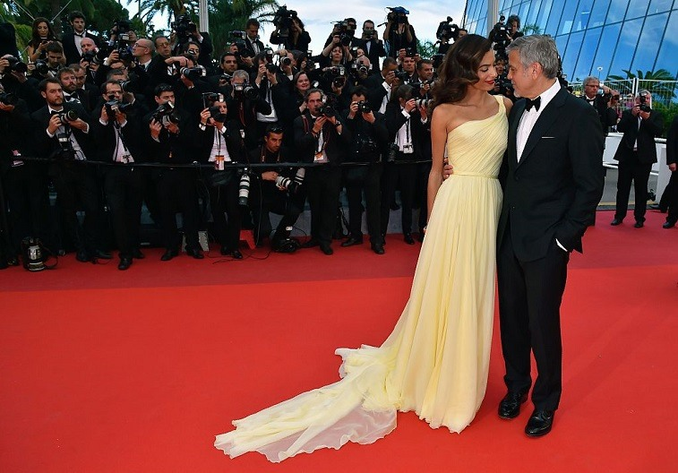 """US actor George Clooney (R), and his wife British-Lebanese lawyer Amal Clooney pose on May 12, 2016 as they arrive for the screening of the film """"Money Monster"""" at the 69th Cannes Film Festival in Cannes, southern France."""