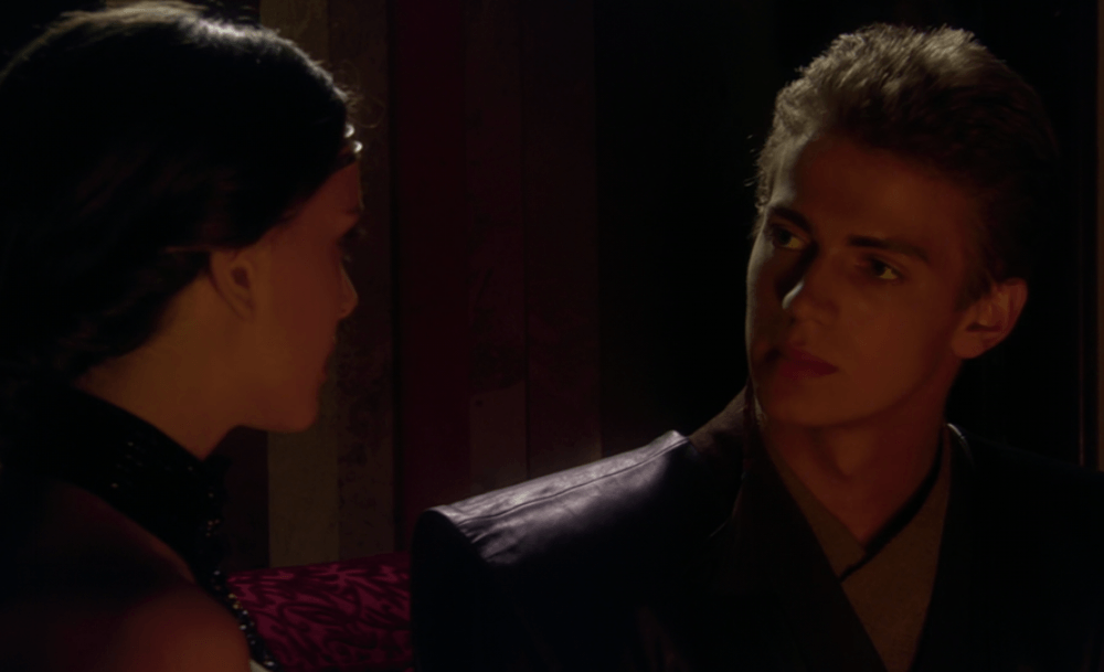 Anakin and Padme talk to each other near the fireplace.