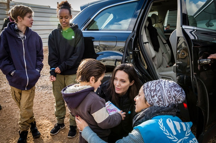 Angelina Jolie, accompanied on the trip by daughters Shiloh, 11, and Zahara, 13, speaks with a young Syrian refugee boy outside his home January 28, 2018 in Zaatari refugee camp, Jordan.