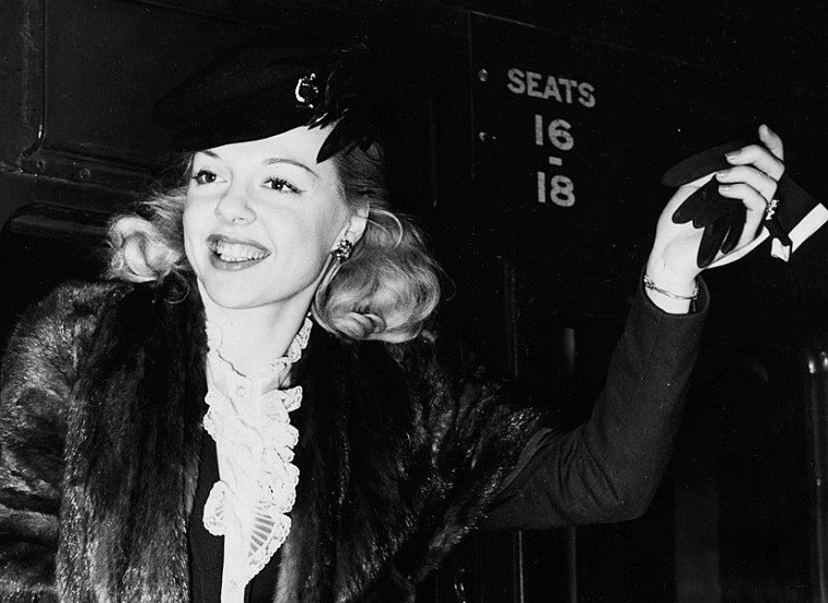 Actress Barbara Perry waving a glove as she arrives at Waterloo Station, London, August 3rd 1951.
