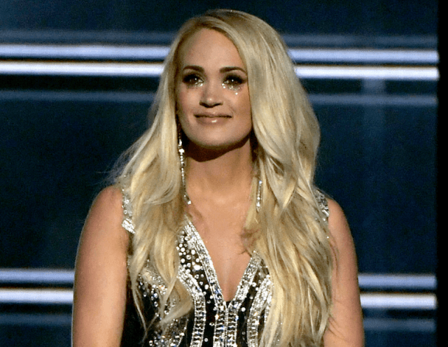 Carrie underwood on stage with a black gown and glittery makeup.