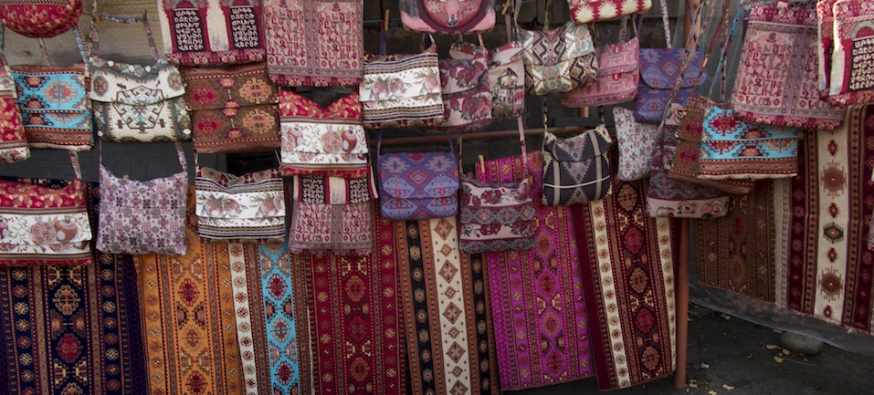colorful fabrics and other folk products at a roadside stall