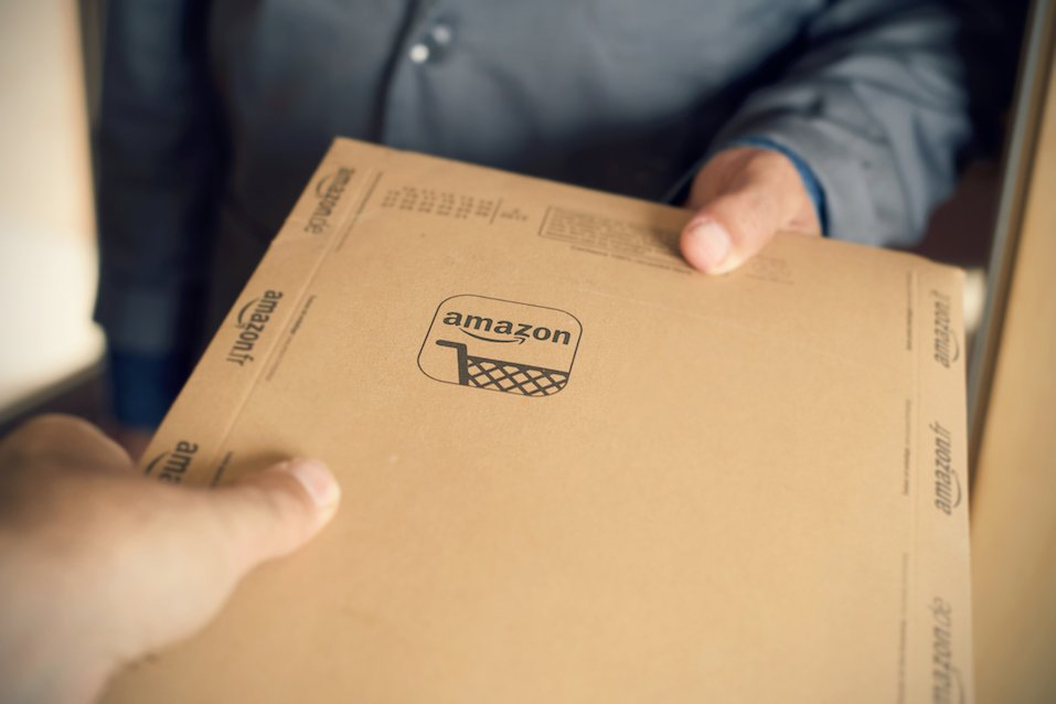 courier delivers an Amazon package to a costumer