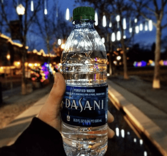 A person holds a bottle of Dasani.