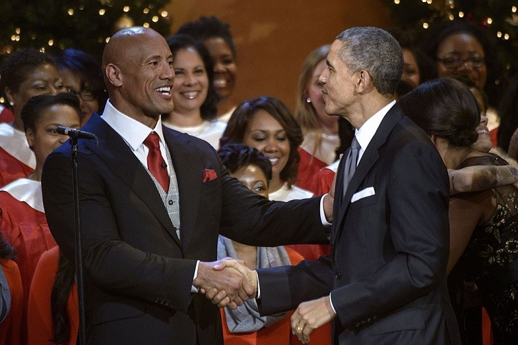 """Dwayne """"The Rock"""" Johnson and US President Barack Obama shake hands during a taping of the Christmas in Washington concert at the National Building Museum December 14, 2014 in Washington, DC. Obama and the first family attended the charity concert to benefit the Children's National Medical Center."""
