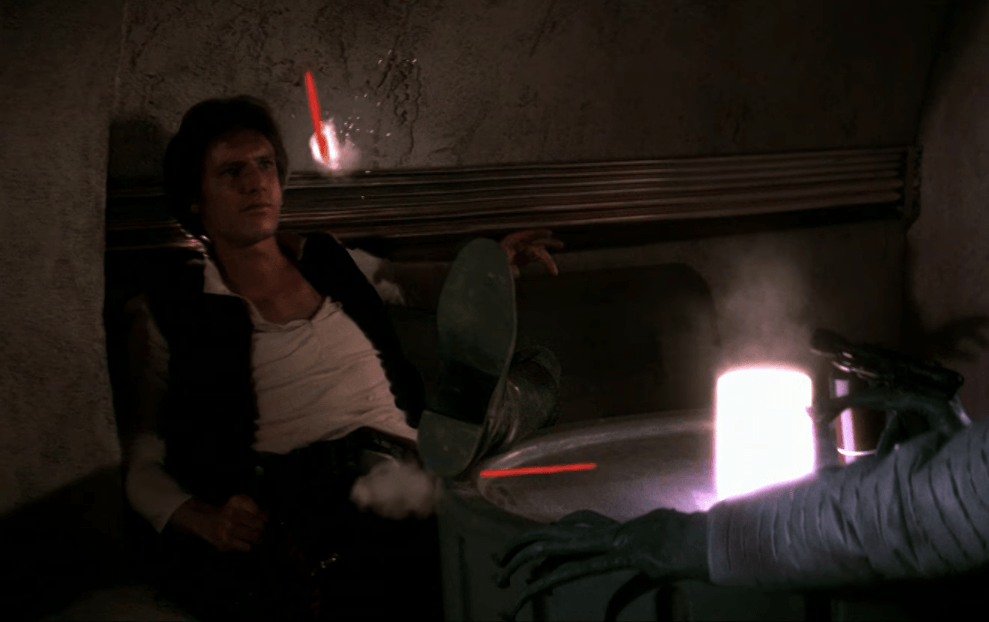 Greedo shoots Han as he sits in front of him.