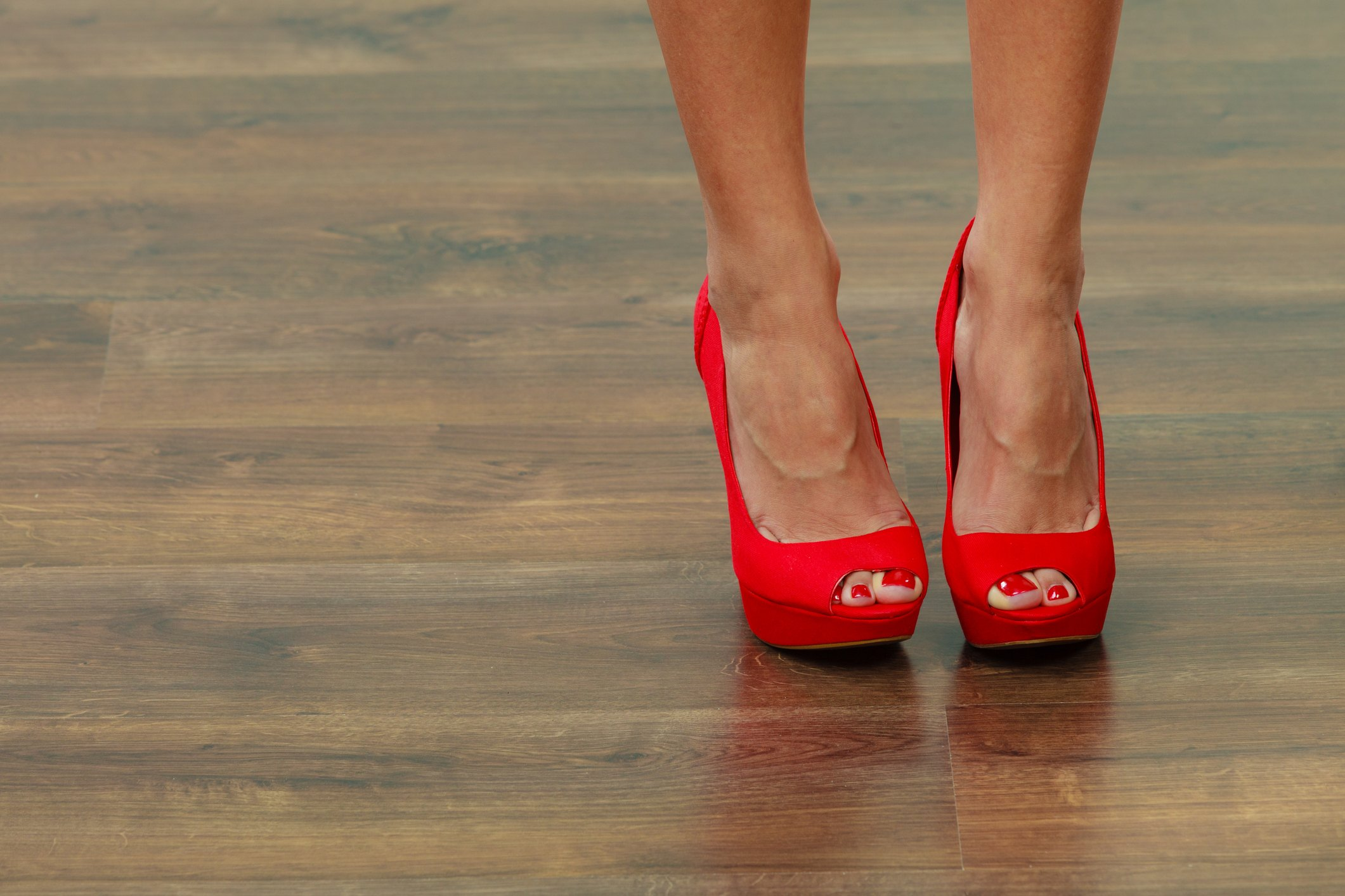 Red high heels on a wood floor