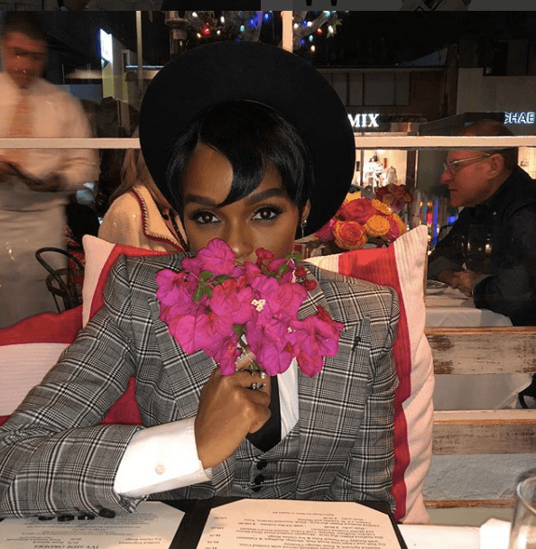 Janelle Monae at a restaurant table sniffing flowers