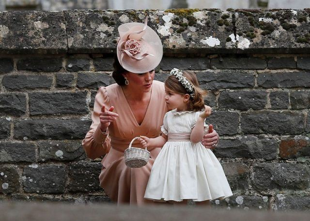 Catherine, Duchess of Cambridge speaks to Princess Charlotte after the wedding of Pippa Middleton and James Matthews at St Mark's Church on May 20, 2017 in in Englefield, England.