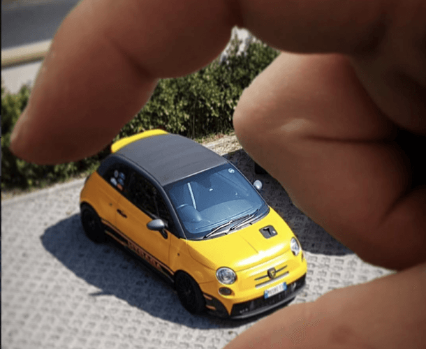 A person plays with a small yellow micro machine car.