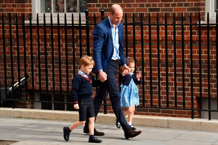 Prince George, Prince William, and Princess Charlotte in front of a hospital.