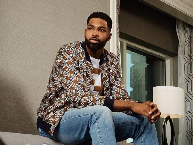 Tristan Thompson sitting on a bench inside a home.