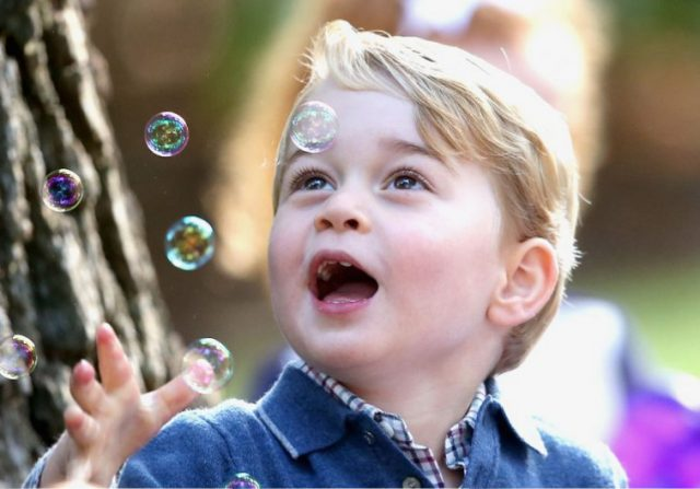 Prince George of Cambridge plays with bubbles at a kid's celebration