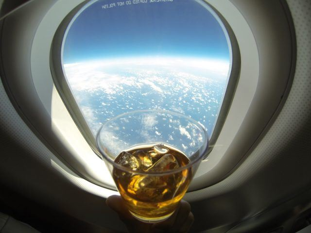 A person drinking beer on a plane.