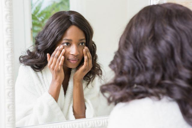A woman looking into a mirror while inspecting her face.