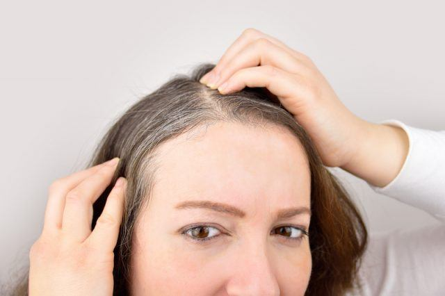 Young woman shows her gray hair