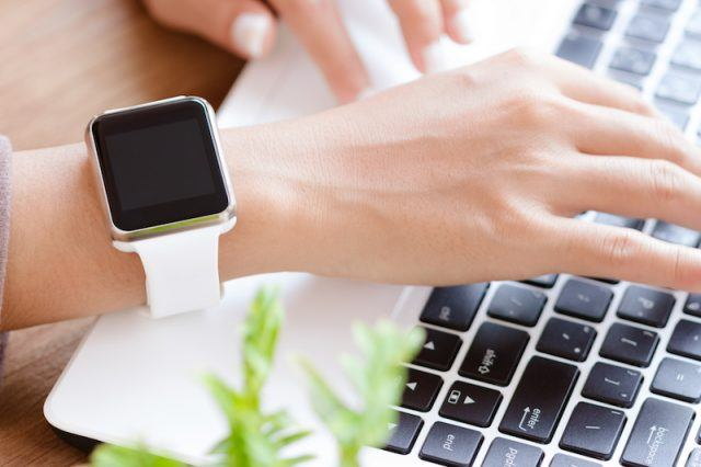 A woman types on her computer while using an Apple Watch.
