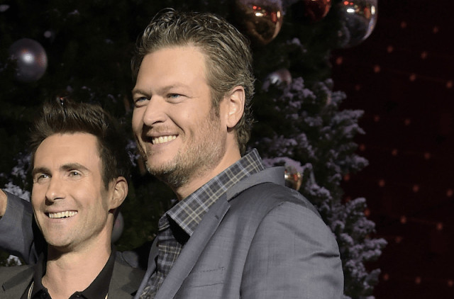 Adam Levine and Blake Shelton smiling together on a red carpet.
