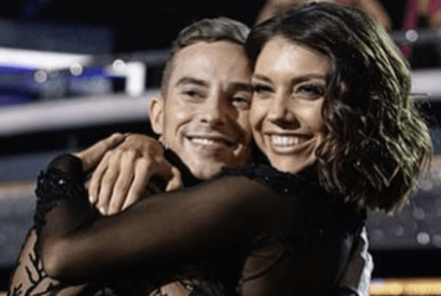 Adam Rippon smiling while hugging Jenna Johnson on the dance floor.