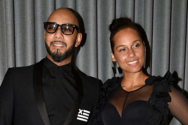 Swizz Beatz and Alicia Keys smiling and posing in front of a gray curtain.