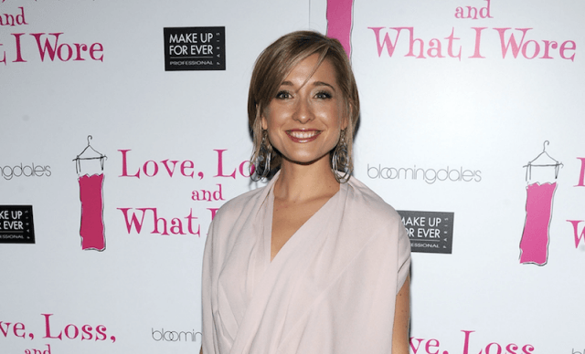 Allison Mack posing on a red carpet.