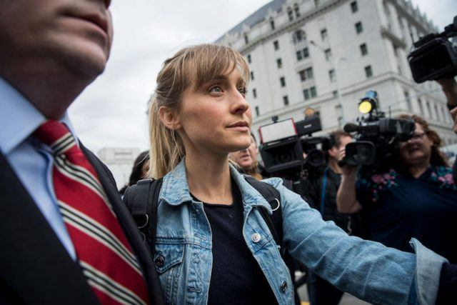 Allison Mack surrounded by reporters.