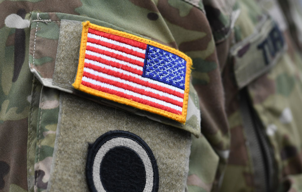 A US flag is pictured on a soldier's uniform