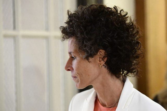 Andrea Constand looking sideways while wearing a white blazer.