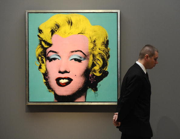 """A guard stands near the painting """"Turquoise Marilyn"""" by Andy Warhol during a media preview on April 1, 2009"""