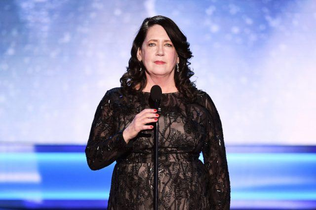 Ann Dowd speaking while wearing a black dress on stage.
