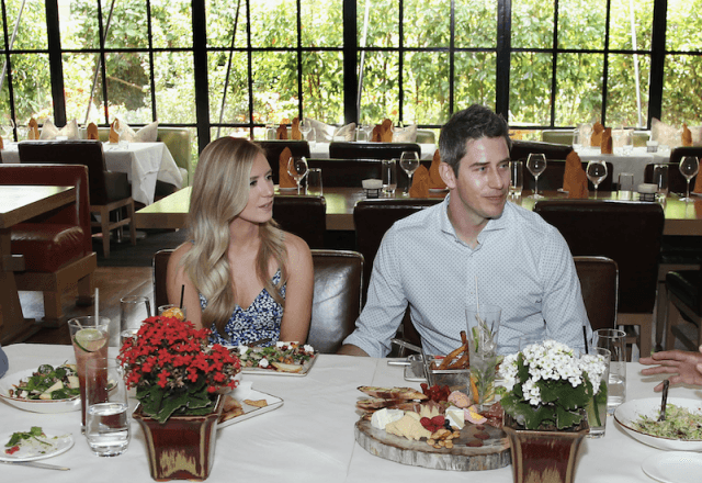 Arie Luyendyk Jr. and Lauren Burnham at a dinner table together.