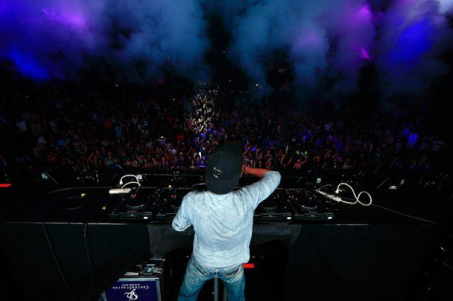 Avicii performing in front of a large crowd.