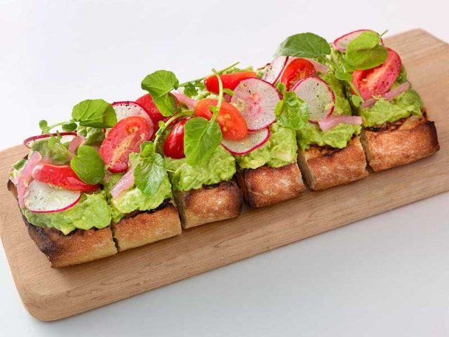 Avocado toast on a wooden board.